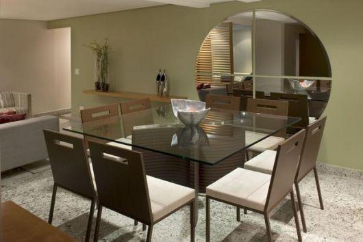 Sala de jantar com parede em tom creme mais escuro, mesa de vidro e cadeiras marrons.