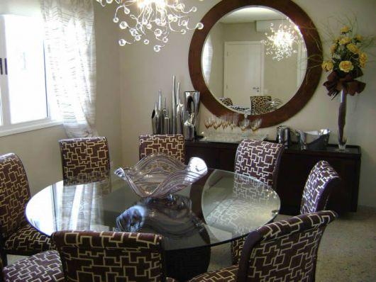 Sala de jantar com mesa redonda, cadeiras marrom estampada, parede com detalhe de espelho redondo com moldura larga marrom.