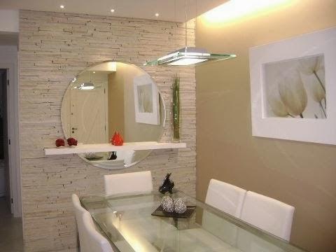 Sala de jantar com parede cinza trabalhada, mesa quadrada e espelho grande redondo.