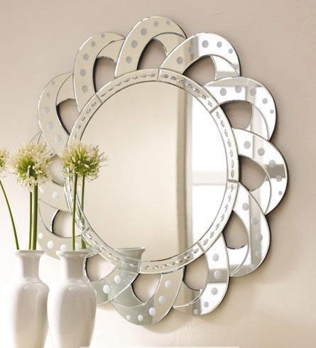Modelo de espelho bistado grande em parede tons pasteis e vaso com flor branca.