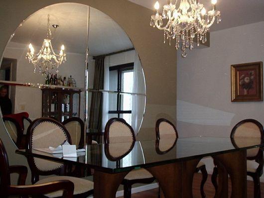 ESpelho redondo bisotado em sala de jantar clean com lustre e parede em tom pastel.