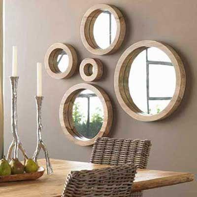 Molduras de madeiras em espelhos redondos dispostos aleatorios em parede na cor marrom terra.
