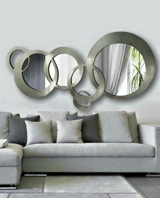 sala com sofa marrom, parede cinza e espelhos redondos com moldura no tom, modelo mais larguinho.