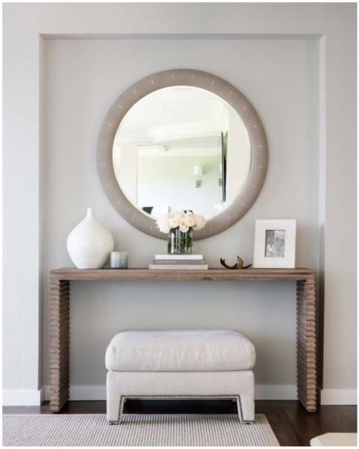 Modelo de espelho redondo com moldura em sala com parede na cor nude, movel de madeira e puff no mesmo tom.