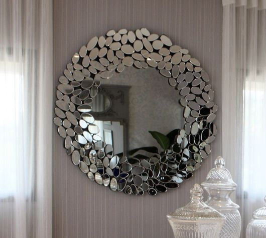Espelho modelo bisotê em parede cinza com cortinas transparentes.