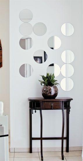 Modelo de espelho pequeno redondo, com movel marrom e vazo de plantas na mesma cor.