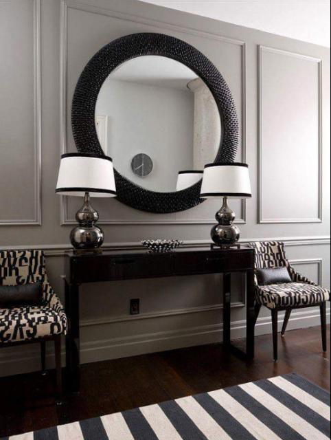 Mini hsall com pare branca, abajures, movel e espelho com moldura preta.