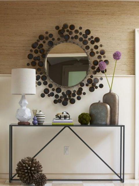 Parede na cor marrom e nude, espelho com moldura de bolinhas e movel de ferro.