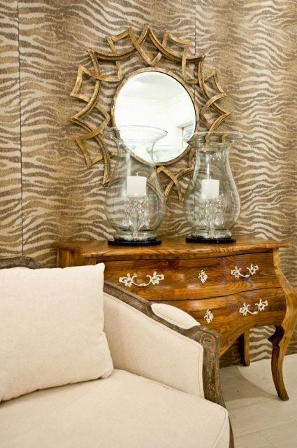 espelho com moldura de sol,parede estampa animal print marrom e nude, sofá.