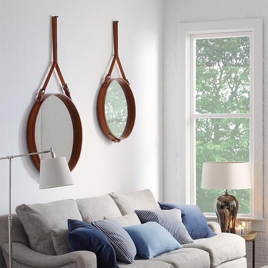 Sala cleans, x=com sofa cinza e espelho de moldura de couro.