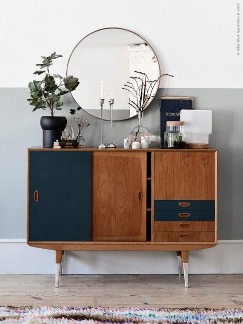 ambiente com parede fundo cinza e branco, com espelho redondo e aparador tom terroso com azul marinho.