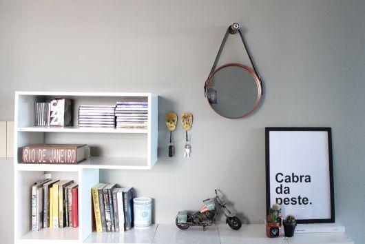 Quarto com parede cinza clarinho, prateleiras e espelho redondo com moldura em couro.
