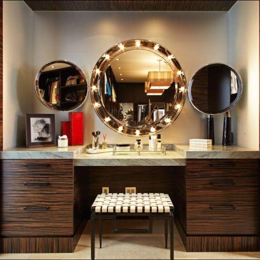 penteadeira marrom, com espelho de luzes em parede ao fundo em tom levemente escuro.
