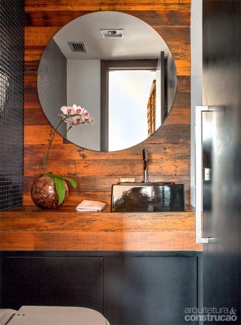 Banheiro preto e cor de madeira, com pia preta e espelho amplo redondo.
