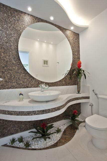 Banheiro clean, com parede de marmore e pia branca com espelho grande.