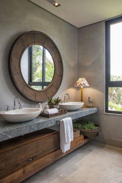 banheiro com espelho de moldura larga amplo, cinza com moveis em madeira marrom.