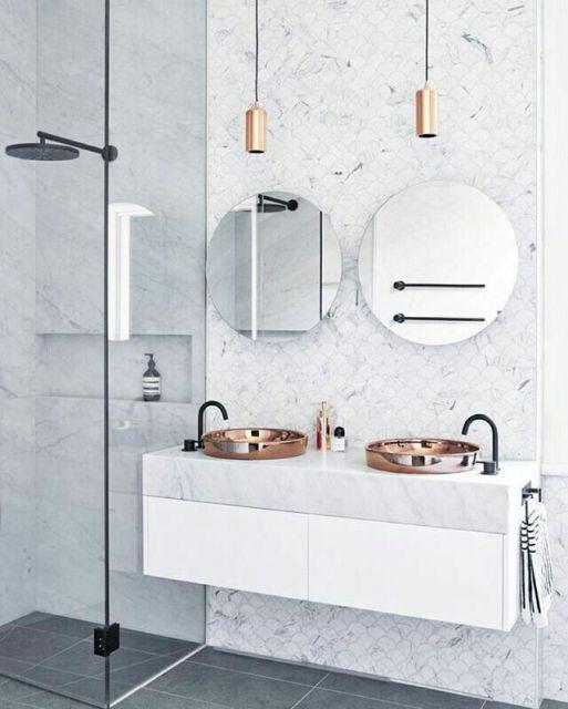 Banheiro clean escandinavo com dois espelhos redondos pequenos e pia de marmore branca.