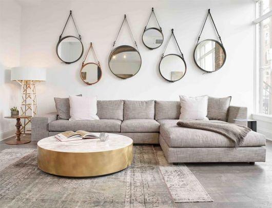 Sala com parede branca, espelhos redondos com moldura de couro, sofa cinza , tapete na mesma cor e mesa de centro de madeira redonda super rústica.