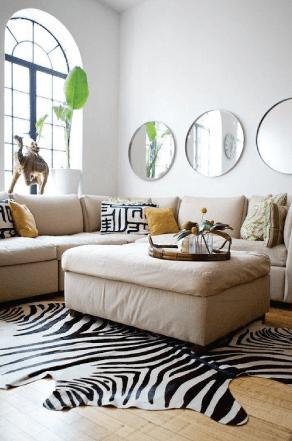 Sala com parede branca, sofá em tons pastéis, tapete estampado em preto e branco (zebra) e espelhos redondos dispostos.