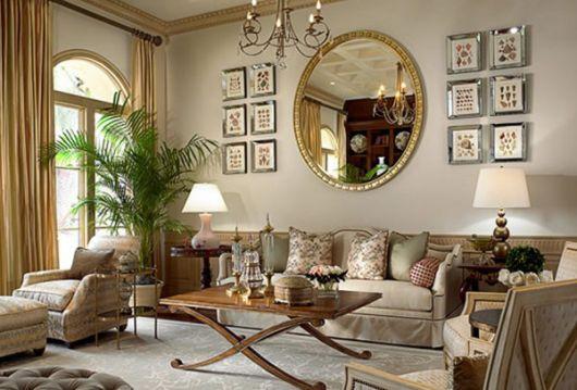 Sala com paredes em tons pasteis, sofa nos mesmos tons e espelho com moldura dourada.