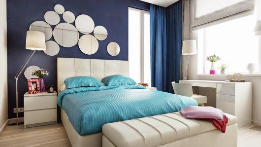 parede azul escuro, cama branca e espelhos dispostos na parede da cabeceira acima da cama.