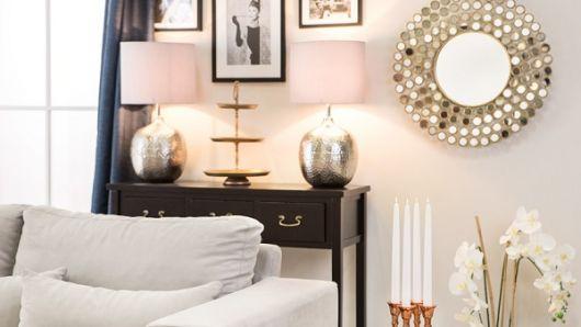 quarto com móvel marrom,cama branca e espelho trabalhado.