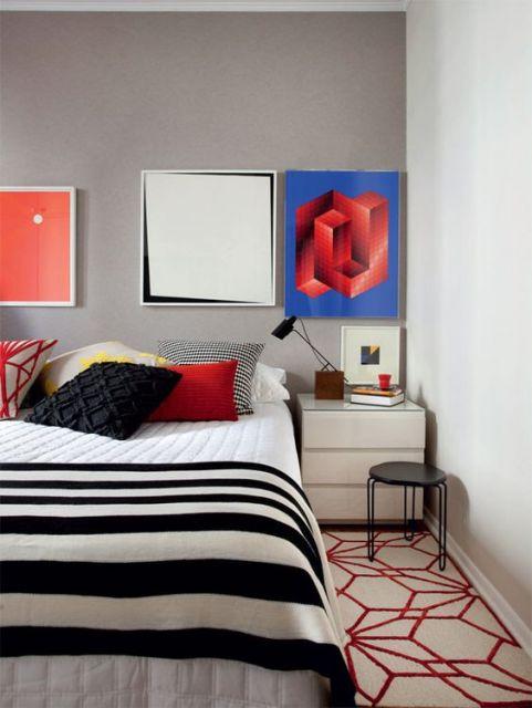 quadros coloridos sobre parede cinza em quarto de casal