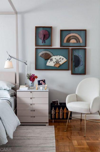 quadros com leques japoneses em quarto de casal