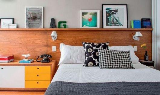 quadros apoiados em prateleira sobre cama de casal