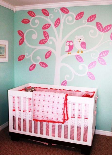 Berço branco encostado em parede azul esverdeada e desenhos rosa.