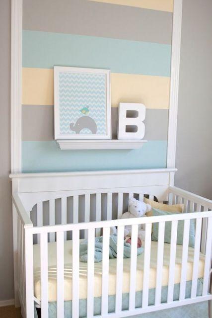 Quarto com berço branco, parede cinza e quadro de paleta de cores.