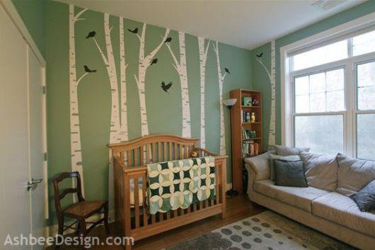 Quarto com piso e móveis de madeira e parede verde com desenho de caules de árvores.