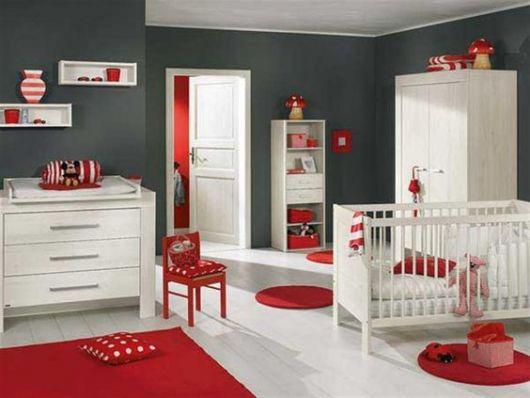 Quarto de bebê com parede cinza escuro, piso e móveis brancos e tapetes e almofadas vermelhas.