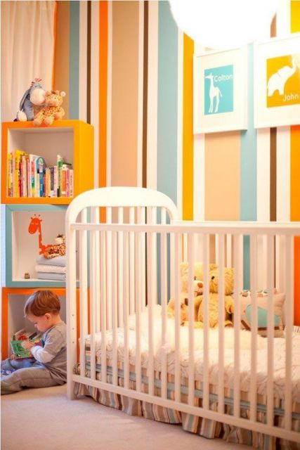 Quarto de bebê com as cores azul claro e laranja.