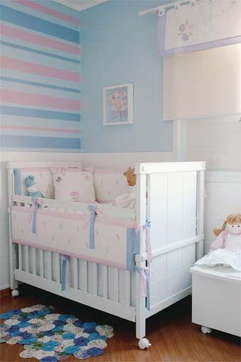 Parede azul claro, com detalhes em rosa e azul mais escuro.