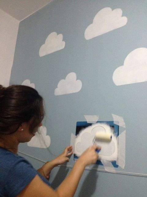 Mulher usando estêncil para fazer nuvens brancas na parede.