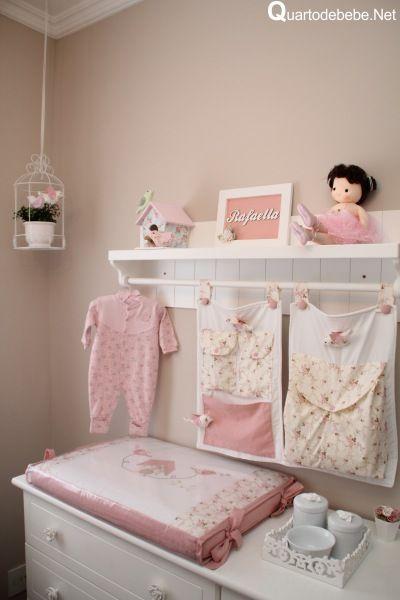 Móvel para trocar o bebê branco, com detalhes e itens decorativos em rosa claro.
