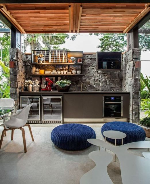cozinha externa feita de pedras com pufs no chão