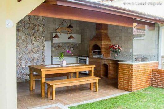 cozinha externa com churrasqueira com mesa e bancos