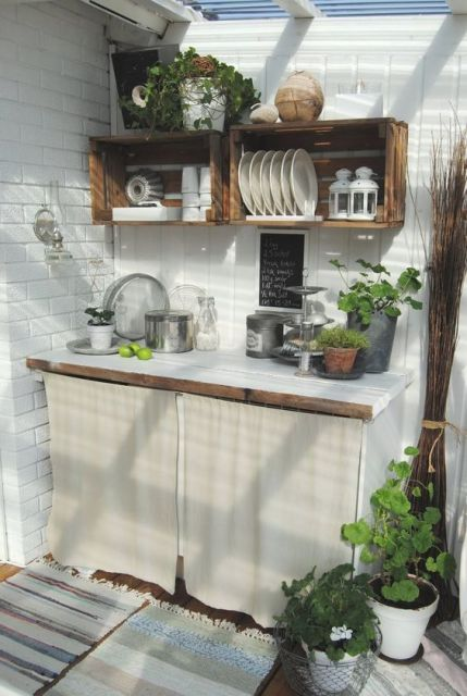 cozinha externa pequena branca com armário fechado com cortinha