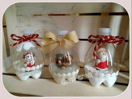 Potinhos feitos com garrafa pet com bonecos natalinos dentro.