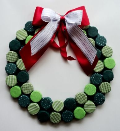Guirlanda feita com tampinhas de garrafas pet encapadas de tecidos verdes.