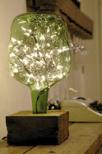 Garrafa com luzes pisca-pisca dentro, formando uma luminária.