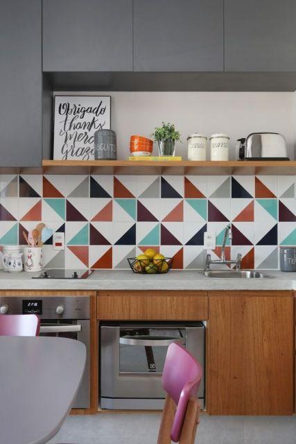 Cozinha com móveis de madeira e papel de parede com triângulos coloridos.