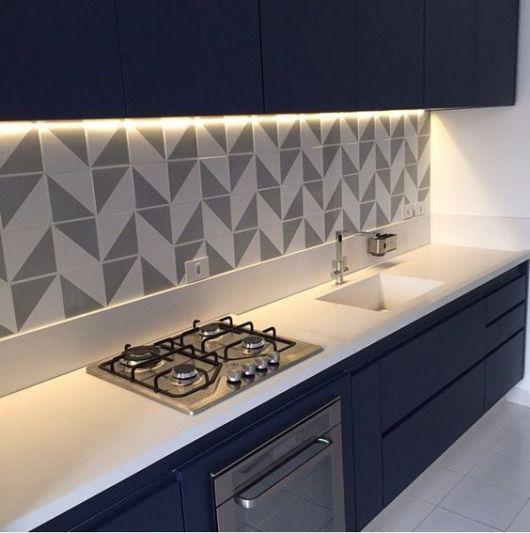 Cozinha com móveis azul escuro e papel de parede com triângulos brancos e cinzas.