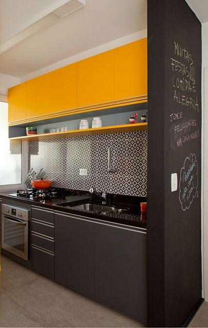 Conzinha preta e mostarda, com papel de parede geométrico.