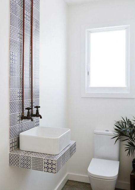 Banheiro com parede da pia com papel de parede geométrico.