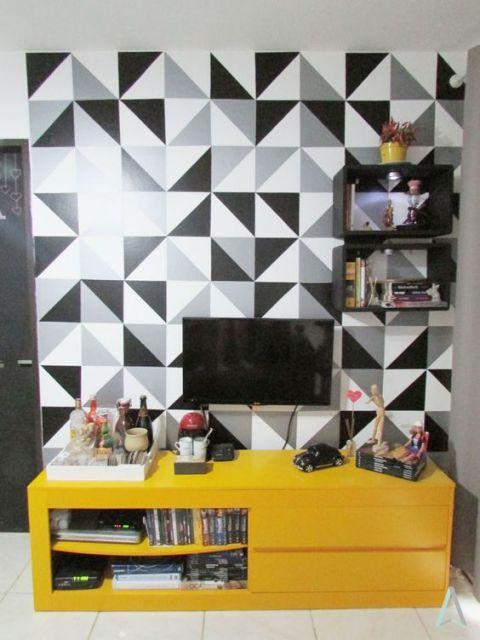 Parede de televisão com triângulos pretos, brancos e cinzas criando um mosaico.