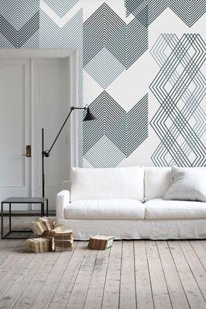 Parede atrás de sofá branco com papel de parede geométrico cinza.