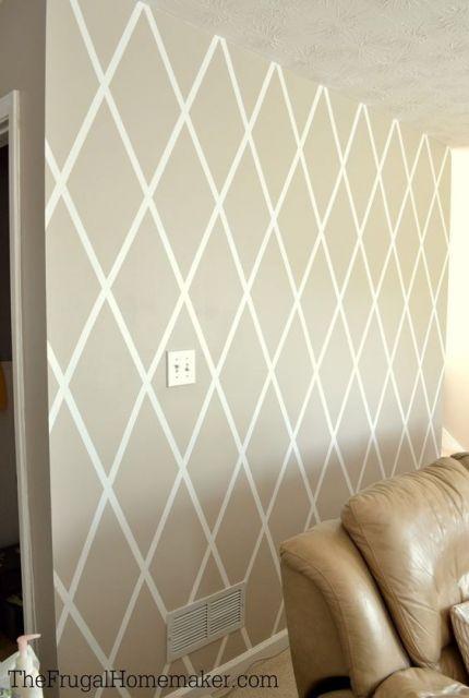 Sala com sofá bege e papel de parede geométrico.